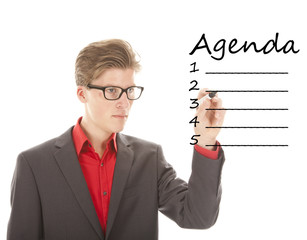 Young man with pen writing an agenda isolated