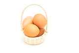 brown eggs in basket on a white background