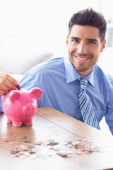 Handsome businessman putting coins into piggy bank looking at ca
