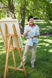 Mature man painting on canvas in park