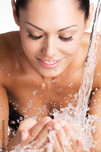 smiling woman washing her face with water