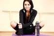 Young smiling fit woman sitting on the yoga mat at gym