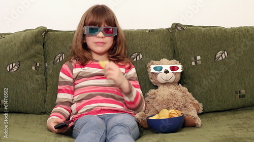 little girl and teddy-bear with 3d glasses watching tv