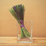 Bouquet of dried lavender flowers in a glass vase on wooden tabl