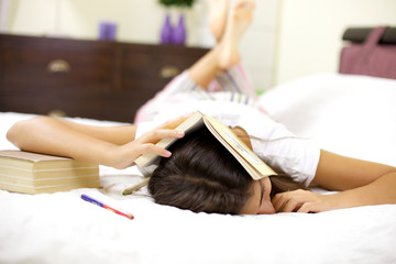 Young woman tired of studying falling asleep in bed