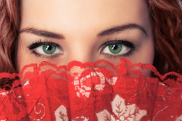 Woman eyes and face hide with red fan