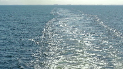 Large wake behind ship with land far away in the distance