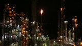 Oil Refinery at Night with Flame