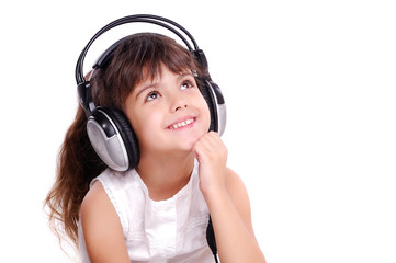 Little girl in headphones looking to the copy space area