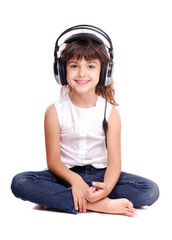 Little girl in headphones sitting on the floor