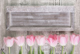 Wooden board with a row of pink tulips
