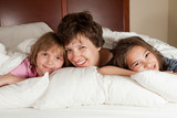 Mother and two daughters in bed