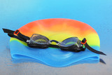 Swim cap and goggles on silver background