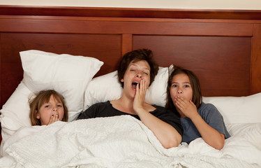 Mother and two daughters in bed yawning