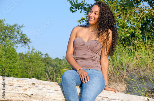 beautiful teen on weathered log