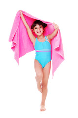 Girl in a swimsuit holding a towel and jumping