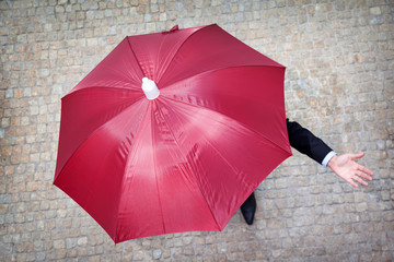 Businessman hidden under umbrella and checking if it's raining