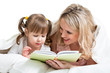 mom reading to kid a book in the bed
