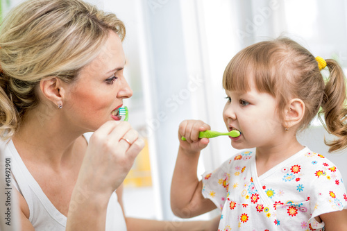 mother and kid daughter brushing teeth in bathroom