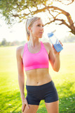 Athletic young woman runner drinking water
