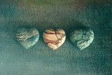 Three stone hearts on wood