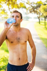 Athletic young man drinking water after workout