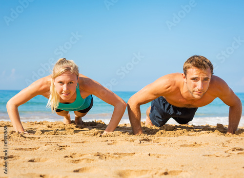 Couple doing push ups on the beac