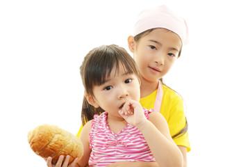 パンを食べる笑顔の姉妹