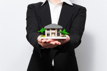 家の模型を差し出す女性