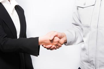 握手するスーツの女性と作業服の男性