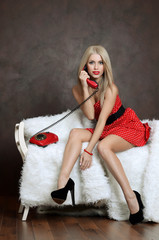 The beautiful woman in a red dress with old phone