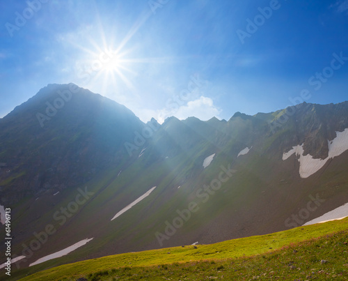 sparkle sun above a mountain pass