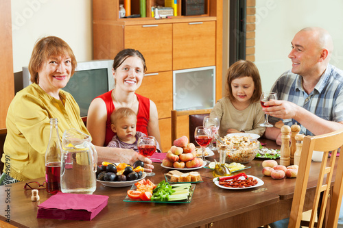 multigeneration family  together over celebratory table