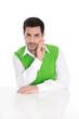 Portrait Business Mann in Grün sitzend am Schreibtisch