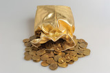 Gold sack with scattered coins on gray background
