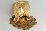 Gold sack with scattered coins on gray