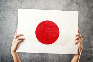 Japan flag. Man holding banner with Japanese Flag.