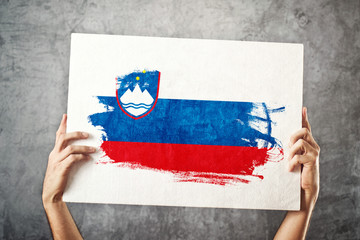 Slovenia flag. Man holding banner with Slovenian Flag.
