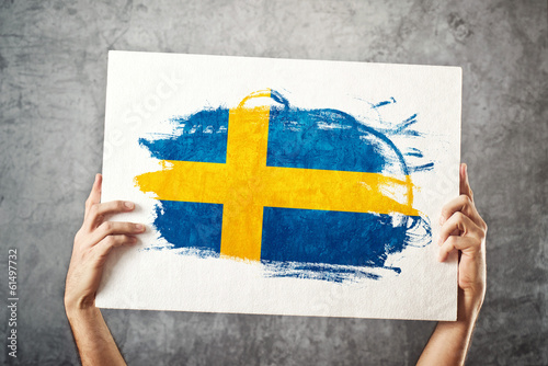 Sweden flag. Man holding banner with Swedish Flag.