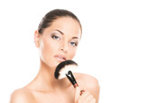 Beauty portrait of a young and healthy woman with a makeup brush