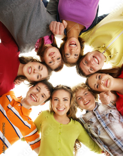 Group of smiling happy teenagers isolated on white