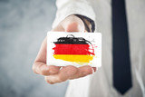 German Businessman holding business card with Germany Flag