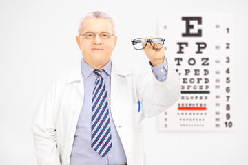 Male optician holding glasses in front of an eye chart