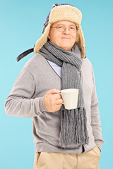 Mature man in winter clothes holding a cup of tea