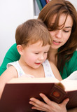 Mother is reading book with her son