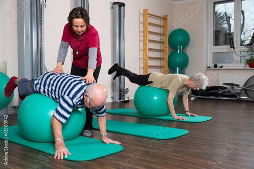 canvas print picture Physiotherapeutin übt mit Senioren