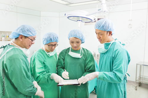 surgeons discussing about something in operating theater