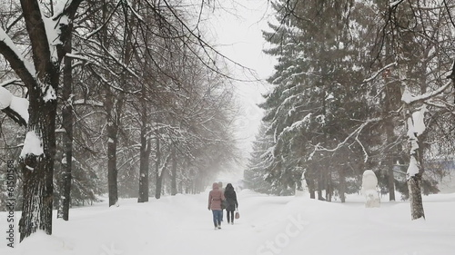 pedestrians walk on the sidewalk in a blizzard