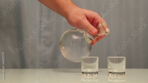 hand pouring vodka into glasses from carafe