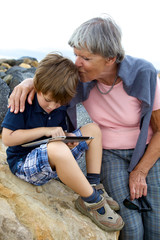 Grandma kissing with love grandson playing with tablet